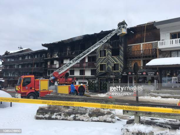 TOPSHOT Firefighters and French gendarmes stand in front of a building destroyed by a major fire which killed two people and injured 22 more on...