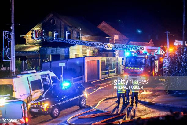 Firefighters and gendarmes stand in front of a house in EstreeBlanche northern France on early January 7 after a fire caused the death of four...