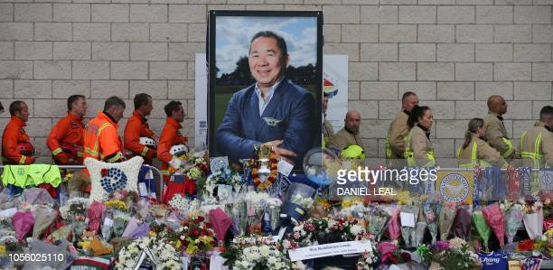 Firefighters and members of a rescue team walk around a portrait of Leicester City Football Club's Thai chairman Vichai Srivaddhanaprabha among the...