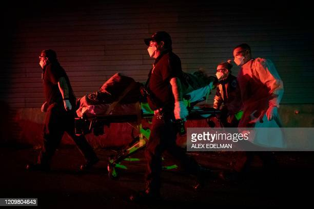 TOPSHOT Firefighters and paramedics with Anne Arundel County Fire Department transport a patient on a stretcher on April 13 2020 in Glen Burnie...
