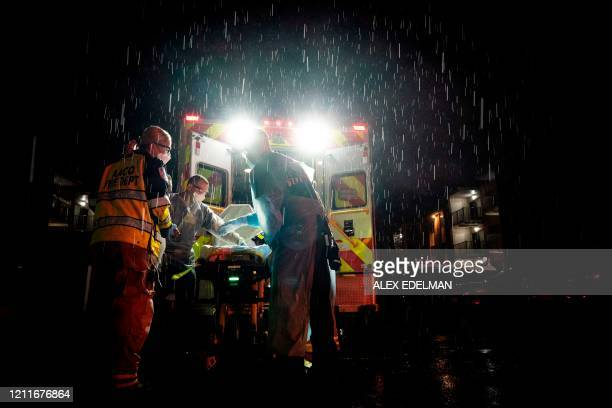 Firefighters and paramedics with Anne Arundel County Fire Department wear enhanced PPE while preparing to transport a suspected novel coronavirus,...