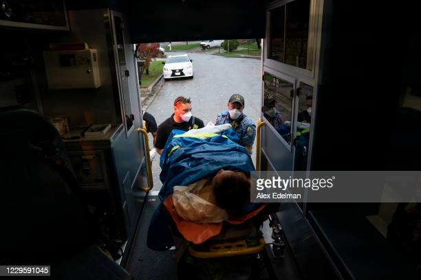 Firefighters and paramedics with Anne Arundel County Fire Department load a patient into an ambulance while responding to a 911 emergency call on...
