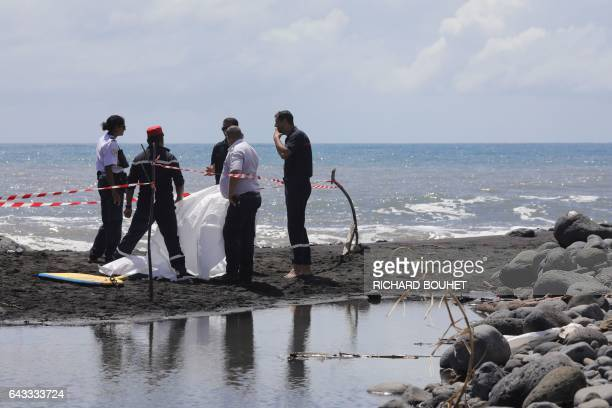 Firefighters and police gather around the body of a bodyboarder killed by a shark hidden by a white cloth on February 21 2017 on a beach in...
