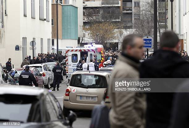 Firefighters and police officers gather in front of the offices of the French satirical newspaper Charlie Hebdo in Paris on January 7 after armed...