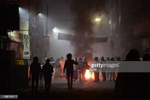 Firefighters and police personnel stand next to burning objects set on fire during demonstrations against India's new citizenship law in Kanpur on...