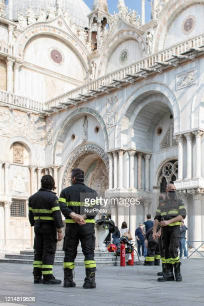 Firefighters and police surround St. Mark's Basilica for a bomb alarm in Venice on May 23, 2020