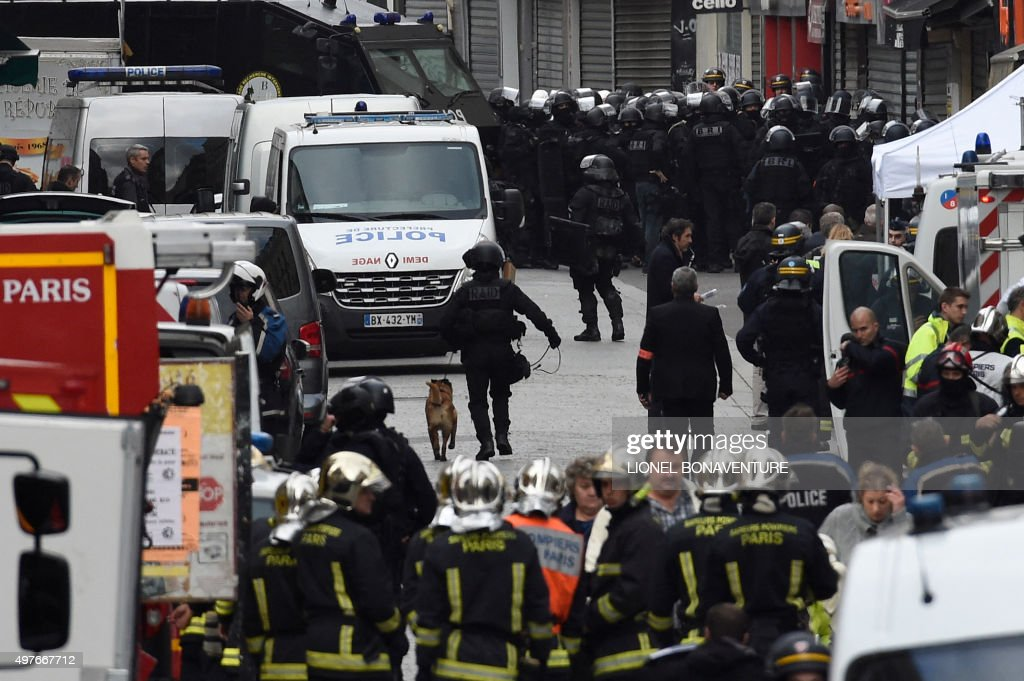 Firefighters and policemen are gathered in the northern Paris suburb of Saint-Denis city center, on November 18, 2015, as French Police special forces raid an appartment, hunting those behind the attacks that claimed 129 lives in the French capital five days ago. At least one person was killed in an apartment targeted in the operation aimed at the suspected mastermind of the attacks, Belgian Abdelhamid Abaaoud, and police had been wounded in the shootout.