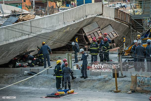 Firefighters and policemen work at the site where several vehicles were crushed by a viaduct that collapsed in Belo Horizonte, Brazil, on July 3,...