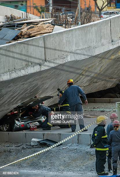 Firefighters and policemen work at the site where several vehicles were crushed by a viaduct that collapsed in Belo Horizonte Brazil on July 3 2014...
