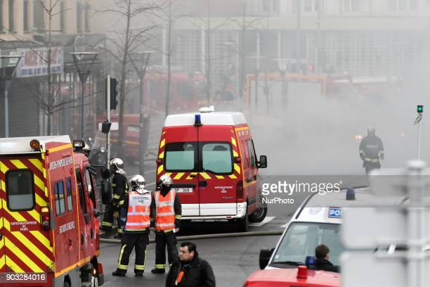 Firefighters and policemen work in ChoisyleRoi southern Paris on January 10 to put out two fires in the basement of two buildings which obliged to...