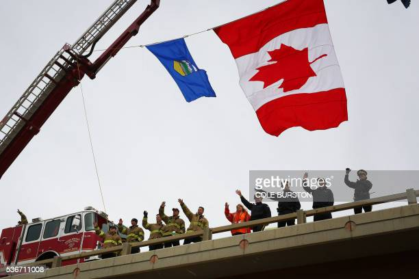 Firefighters and RCMP officers greet Fort McMurray residents from an overpass on Highway 63 just outside Fort McMurray Alberta on June 1 2016 Tens of...