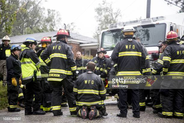 Firefighters and rescue crew stand in front of a home after removing a resident trapped inside due to a fallen tree during Hurricane Florence in...