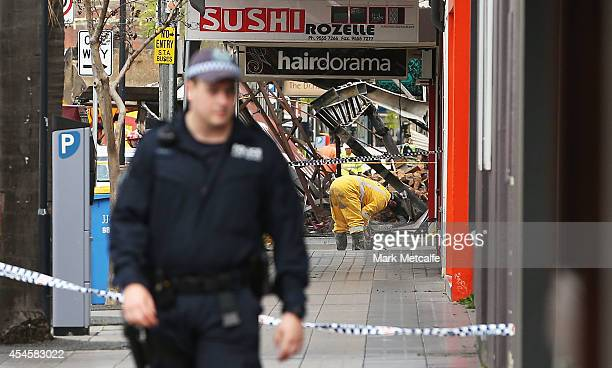 Firefighters and rescue crew work at the scene of a shop explosion in Darling Street on September 4 2014 in Sydney Australia Three people have been...