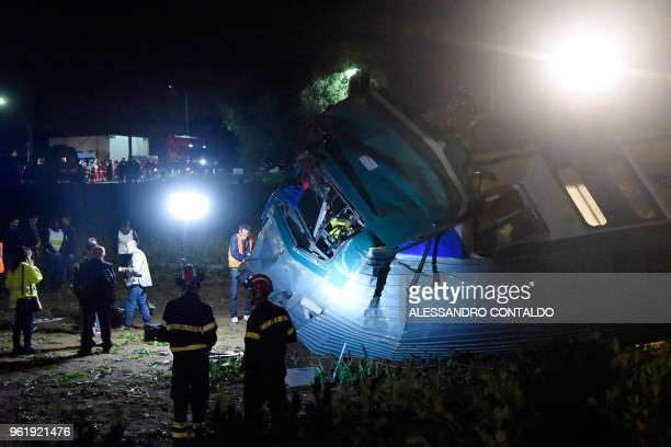 Firefighters and rescue personnel are seen at the the site of a crash after a regional train plowed into a truck that had stopped on the tracks in...