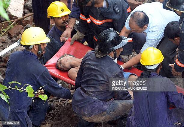 Firefighters and rescue workers bring out a survivor from under the rubble of a collapsed building in Mumbai on September 27 2013 A fivestorey...