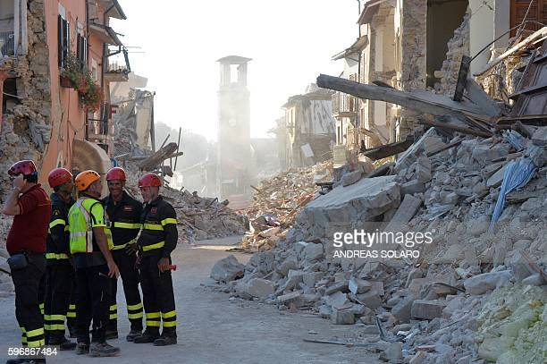 Firefighters and rescue workers stand near the damaged Sant'Agostino church and rubble and debris of damaged buildings in the central Italian village...