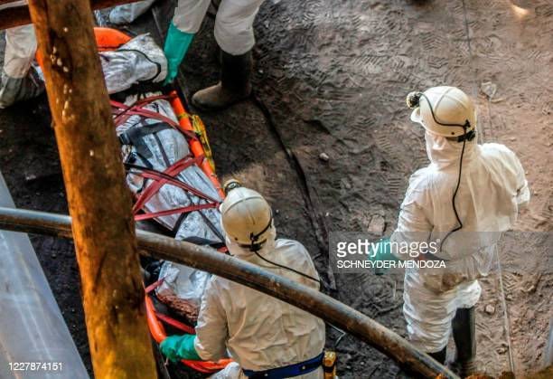 TOPSHOT Firefighters and rescuers carry the body of one of the miners at the entrance of the El Cedro coal mine in the municipality of El Zulia Norte...