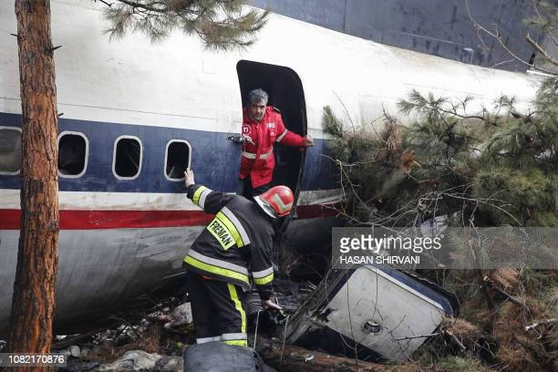 Firefighters and security forces gather amidst the debris of a Boeing 707 cargo plane that reportedly crashed into a residential complex near the...