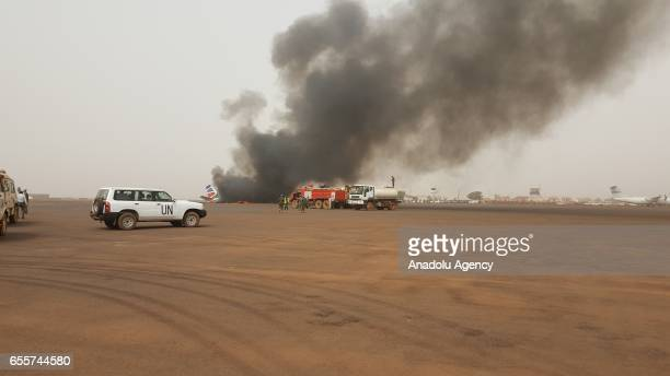 Firefighters and soldiers belonging to United Nations Mission in South Sudan try to extinguish the fire at the plane, which took off from Juba with...