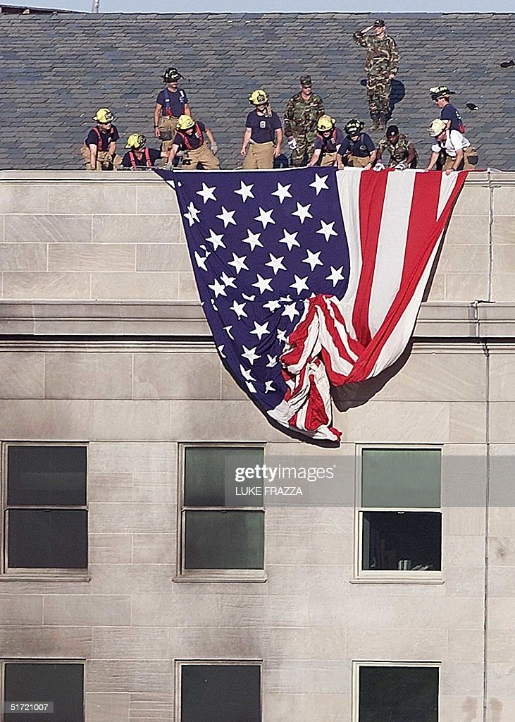 Firefighters and soldiers unfurl an American flag from the roof of the damaged side of the Pentagon in Washington 12 September 2001, one day after a hijacked airplane crashed into the Pentagon causing extensive damage and loss of life. AFP PHOTO/Luke FRAZZA
