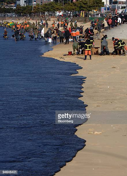 Firefighters and villagers clean up the crude oil leaked from the supertanker Hebei Spirit on Mallipo beach in Taean South Korea on Saturday Dec 8...