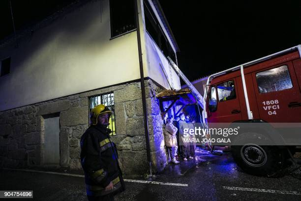 Firefighters and villagers stand outside the building of a local community centre where a fire killed eight people and injured 50 others in Vila Nova...
