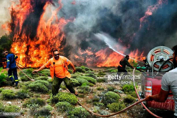 TOPSHOT Firefighters and volunteers try to extinguish flames during a wildfire at the village of Kineta near Athens on July 24 2018 Raging wildfires...