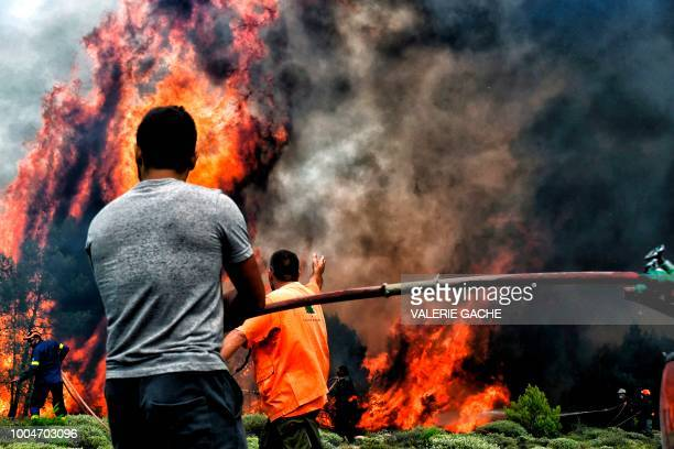 Firefighters and volunteers try to extinguish flames during a wildfire at the village of Kineta near Athens on July 24 2018 Raging wildfires killed...