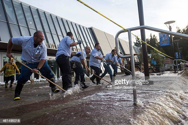 Firefighters and workers clear mud and water at Edwin W Pauley Pavilion after a major water main break sent a geyser of water blasting through Sunset...
