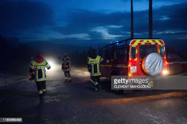Firefighters are at work near the site where a helicopter from the civil security services crashed while on a rescue mission for flood victims in the...