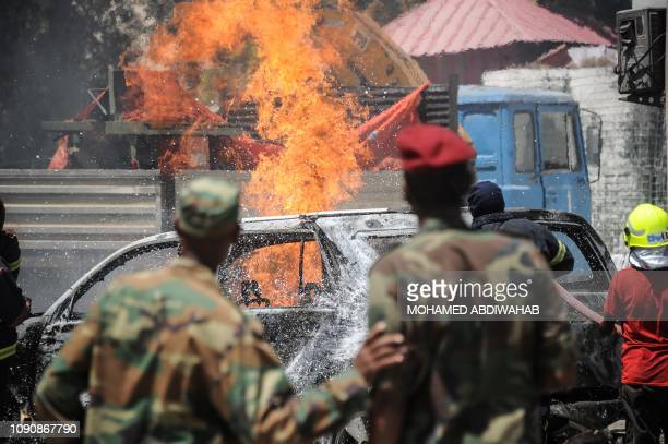 TOPSHOT Firefighters are at work to extinguish a fire at the scene where a car bomb exploded in Mogadishu on January 29 20 19 Two people were killed...