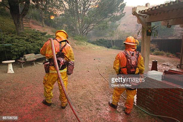 Firefighters are covered with red PhosCheck fire retardant dropped by a firefighting airtanker on the house they are protecting as wildfire closes in...