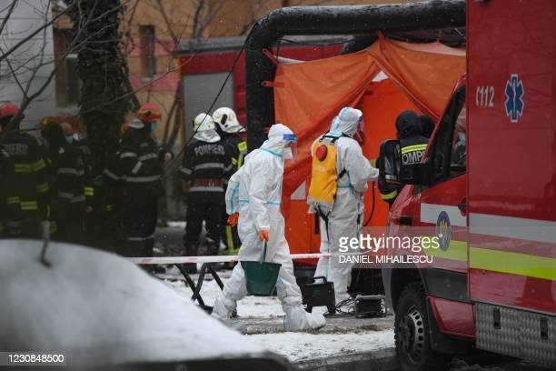 Firefighters are pictured outside the Matei Bals infectious diseases hospital in Bucharest on January 29, 2021 where at least four people died after...
