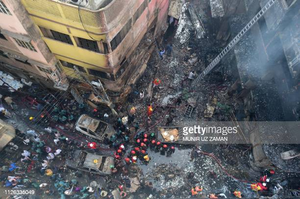 TOPSHOT Firefighters are seen at the scene of a fire in Dhaka on February 21 2019 At least 69 people have died in a huge blaze that tore through...