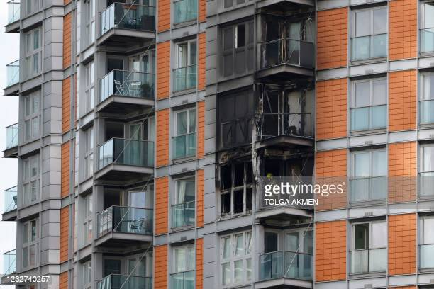 Firefighters are seen at work in burned flats in a residential tower block in east London on May 7, 2021 following a fire. - Over 100 firefighters...