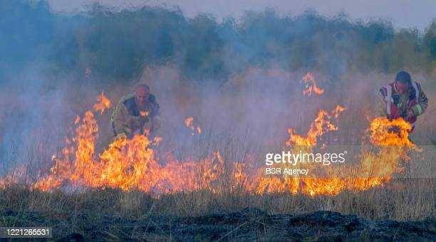 Firefighters are seen extinguishing a wildfire in Bargerveen nature reserve on April 26, 2020 in Zwartemeer, Netherlands.