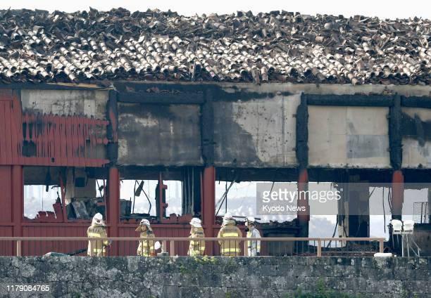 Firefighters are seen in front of the Hokuden north hall of Shuri Castle in Naha Okinawa Prefecture southern Japan on Oct 31 after it burned down in...