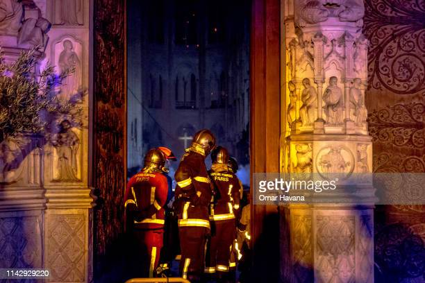Firefighters are seen inside famed Notre-Dame Cathedral assessing the damage caused by fire on April 15, 2019 in Paris, France. A fire broke out on...