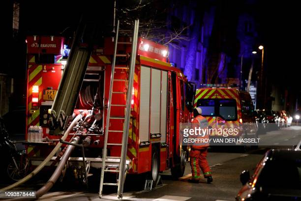Firefighters are seen near a building that caught fire in the 16th arrondissement in Paris on February 5 2019 Seven people died and another was...