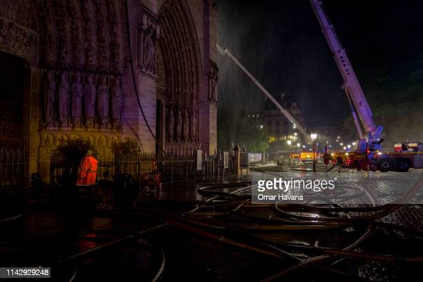 Firefighters are seen outside famed NotreDame Cathedral working to extinguish the fire in Paris France on April 15 2019 in Paris France A fire broke...