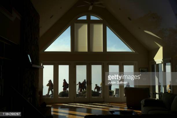 Firefighters are seen through the window of a home as they monitor air operations that are battling the Kincade Fire on October 29 2019 in Healdsburg...