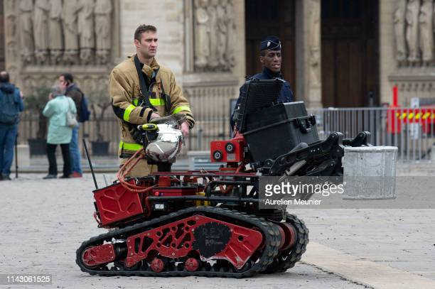 Firefighters are seen with a robot firefighter called Colossus made by French robotics company Shark Robotics outside NotreDame Cathedral after a...