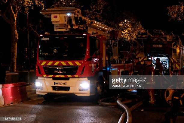 Firefighters are seen working near Notre-Dame Cathedral in Paris early on April 16, 2019. - A huge fire that devastated Notre-Dame Cathedral is...