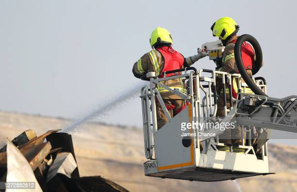 Firefighters are seen working on a collapsed building after a fire broke out at South London's Optima Trade Park on September 15, 2020 in London,...