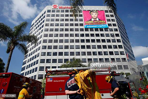 Firefighters arrive as Greenpeace activist have hung a banner on the Mattel headquarters in Los Angeles June 7 2011 Greenpeace is protesting Mattel's...