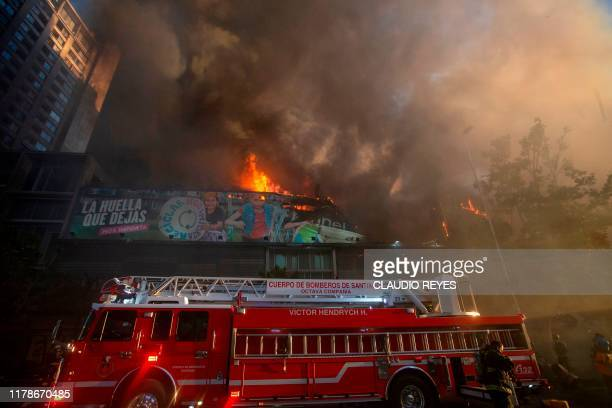 Firefighters arrive at a building on fire moments after a demonstration in Santiago on October 28 2019 Chilean President Sebastian Pinera unveiled a...