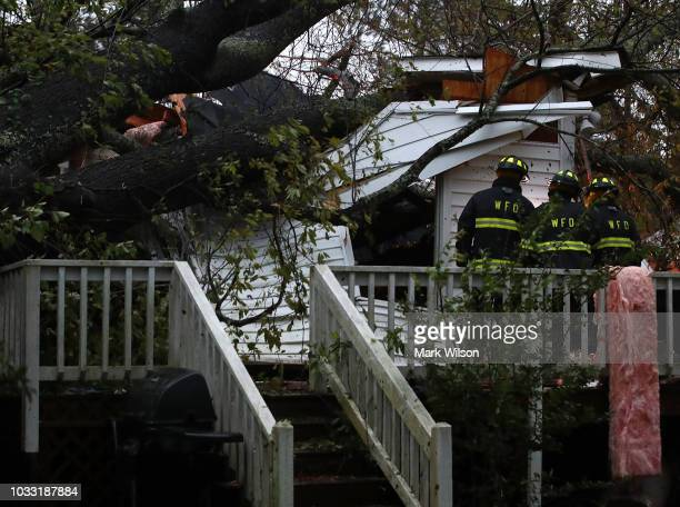 Firefighters arrive at a home where a large tree fell on that had three people trapped after Hurricane Florence hit the area on September 14 2018 in...