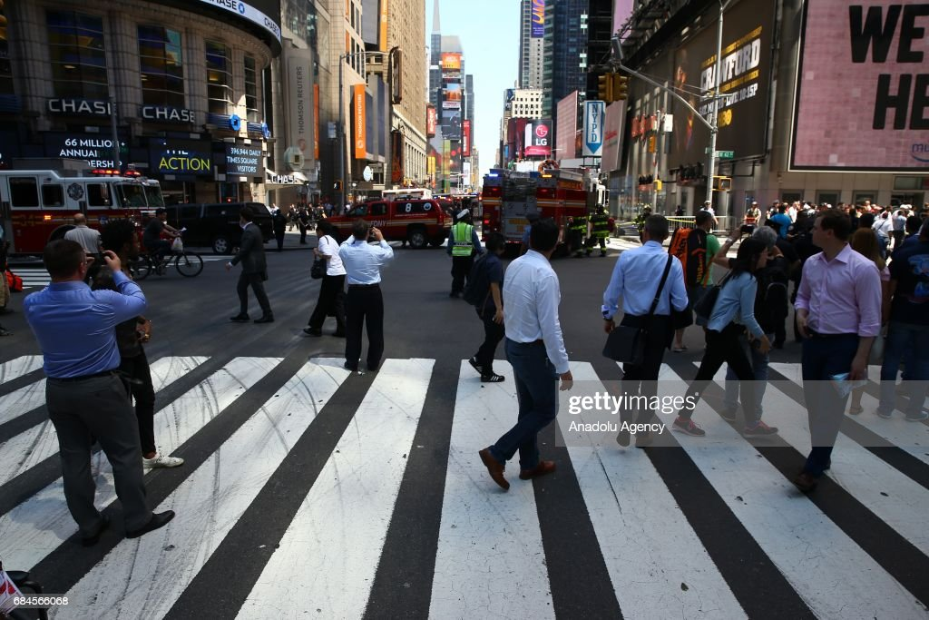 Firefighters arrive to extinguish a wrecked vehicle after it plowed into pedestrians on a busy sidewalk on the corner of West 45th St. and Broadway at Times Square, New York, NY United States on May 18, 2017. Multiple pedestrians were struck Thursday by a speeding vehicle in the heart of New York City, according to reports. At least 1 people dead and 19 others wounded.