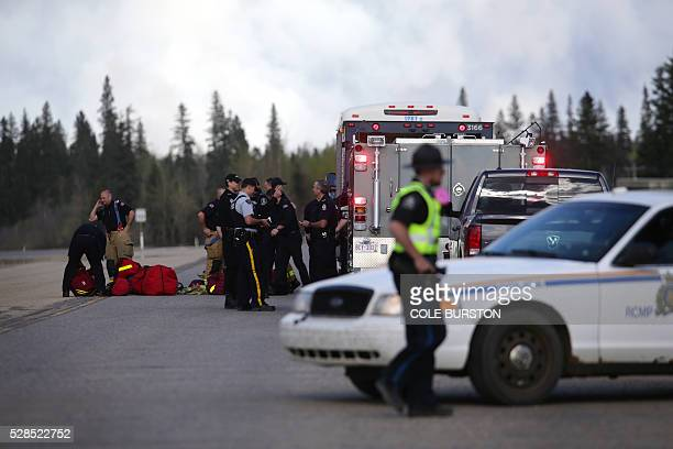Firefighters assemble on Highway 63 near Fort McMurray Alberta on May 5 2016 The Province of Alberta has issued a State of Emergency as more than...