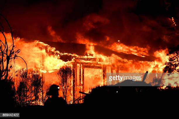 TOPSHOT Firefighters assess the scene as a house burns in the Napa wine region of California on October 9 as multiple winddriven fires continue to...